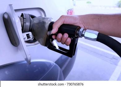 Man hand is holding the oil dispenser.