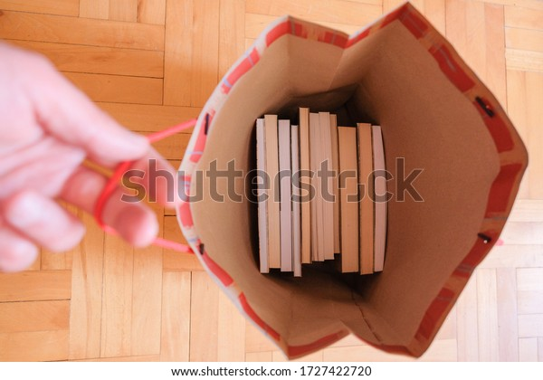 Man hand holding a paper bag full of books