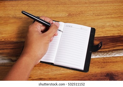 man hand holding a pen ready to write in a notebook