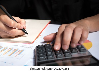 A man hand holding a pen and a record number from the calculator.