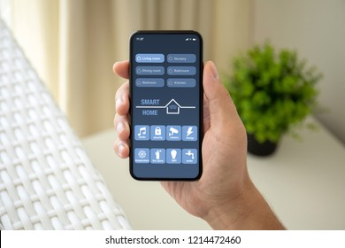 man hand holding phone with app smart home on screen in room house