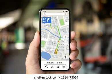 man hand holding phone with app navigation map on screen background of city street