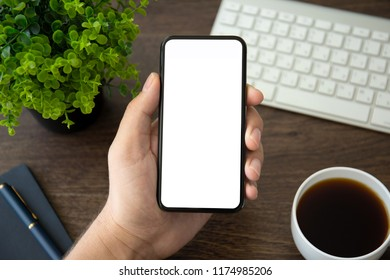 man hand holding phone with isolated screen over table in the office