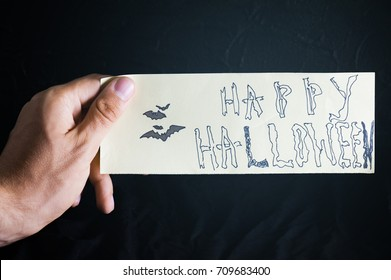 The man hand is holding the piece of paper with text Happy Halloween and drawing bat with cold filter. Concept happy holiday. October time.