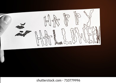 The man hand is holding the piece of paper with text Happy Halloween and drawing bat with warm instagram filter. Concept happy holiday. October time.Black and white filter