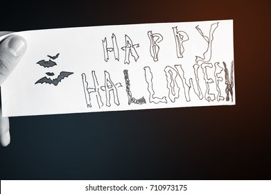The man hand is holding the piece of paper with text Happy Halloween and drawing bat with warm and cold instagram filter. Concept happy holiday. October time.Black and white filter
