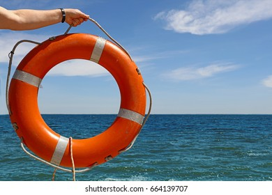 Man hand holding plastic orange color lifebuoy ring over blue sea water and clear sky, close up, low angle view
