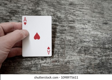 man hand holding playing card ace of hearts with copyspace, casino concept
