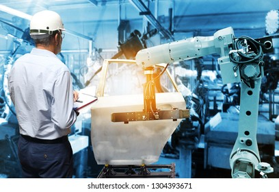 Man hand holding QC check with automate wireless Robot arm in smart factory background. Mixed media of welding robot in the automotive parts industry