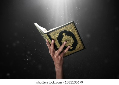 Man hand holding quran holy book