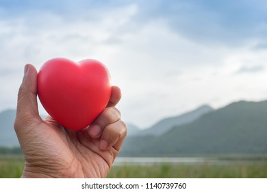 Man Hand holding Red Heart shape rubber model with outdoor mountain background.Image Concept good health.