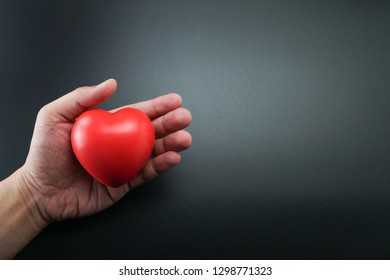 Man Hand holding Red Heart,Concept of Love and Health care,family insurance.World heart day, World health day.Valentine's day.isolated shape of heart on black background.