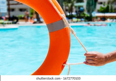 Man hand holding rope of Beach life belt. Beach guard ready for assistance and help.Saving ring equipment on the pool.Rescue necessary lifebuoy aid