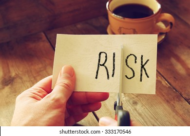 man hand holding scissors and cutting paper card with the word risk .
