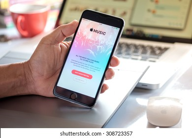 A man hand holding screen Apple music app showing on iPhone 6 plus in his office. Apple Music is the new iTunes-based music streaming service that arrived on iPhone.CHIANG MAI,THAILAND - AUG 23,2015