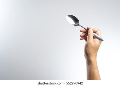 Man hand holding a silver spoon on white background