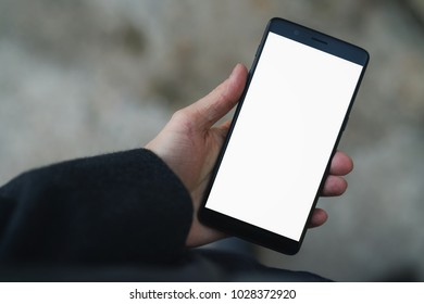 man hand holding smarphone with white screen outdoors in town