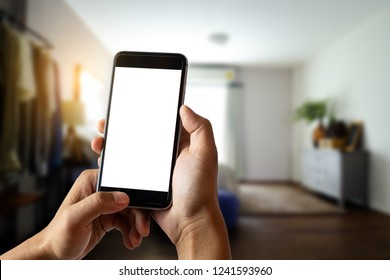 A man hand holding smart phone device in the bright office room interior.