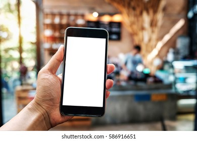 A man hand holding smart phone device in the coffee shop or cafe background.