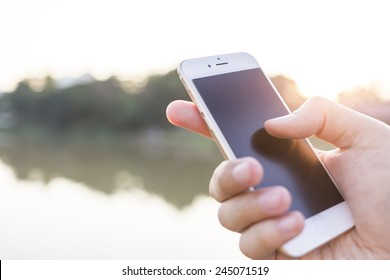 Man hand holding smartphone against on smooth background.