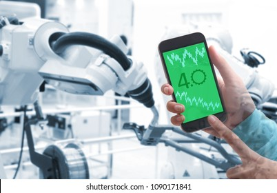 Man hand holding smartphone  with Augmented reality screen software and blue tone of automate wireless Robot arm in smart factory background, Industry 4.0 concept .