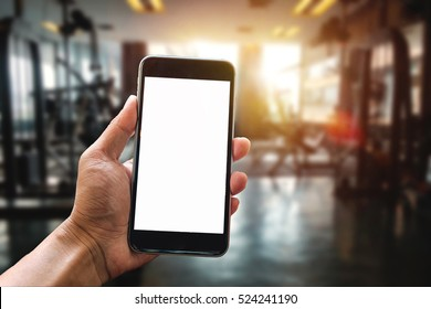 A man hand holding smartphone device at gym background in morning light
