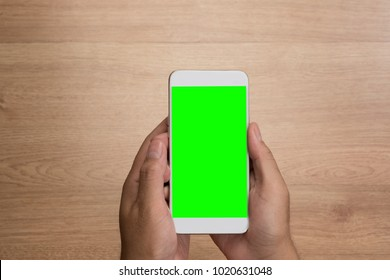 Man hand holding the smartphone with green screen isolated on wooden background.