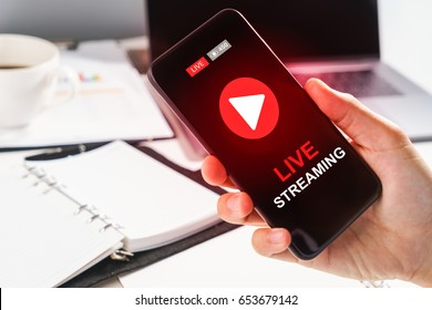 Man Hand Holding Smartphone with Live Streaming with Modern laptop computer .Internet social  marketing concept