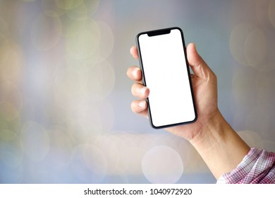 Man hand holding smartphone on abstract bokeh background