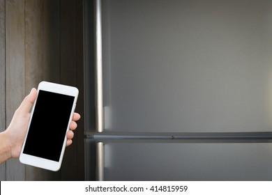 Man hand holding smartphone  on refrigerator