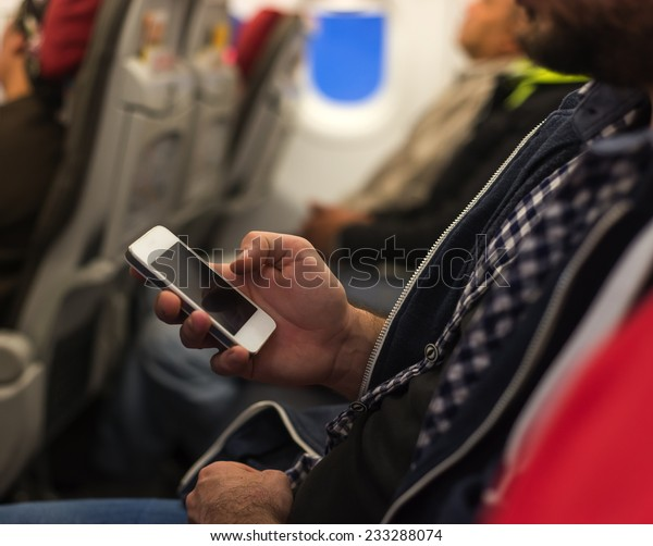 Man hand holding smartphone and texting during flight
