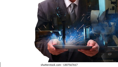 Man hand holding tablet with automate wireless Robot arm in smart factory background. Mixed media of  welding robot  in the automotive parts industry