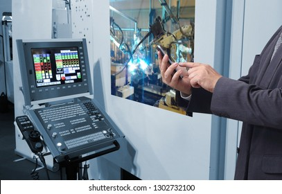 Man hand holding tablet or cell-phoner with automate wireless Robot arm in smart factory background. Mixed media of welding robot in the automotive parts industry