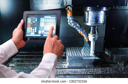 Man hand holding tablet or cell-phoner with automate wireless Robot arm in smart factory background. engine gear drilling machine , industrial blue tone  background