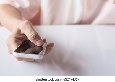 Man hand holding and touching blank screen mobile smart phone  with reflection on white table, close up.
