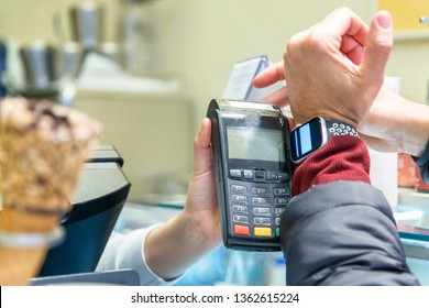 A man hand holding and using of smart watch paying for ice cream to a cashier. Shopping concept.