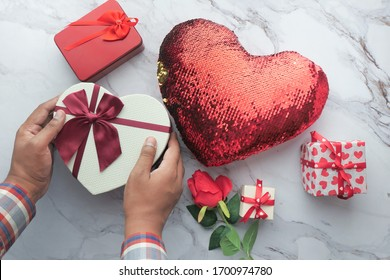 man hand holding valentine gift and envelope