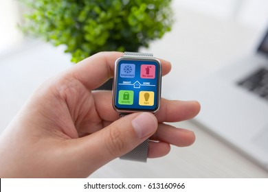 man hand holding watch with app smart home on screen