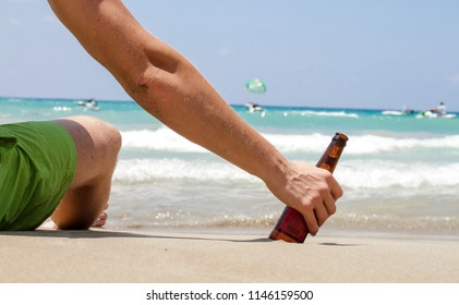 Man hand holds  bottle of beer on the beach (Close up)