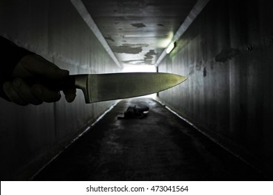 Man hand holds a knife over a murder victim in a dark tunnel. Violence against women concept. Real people, copy space