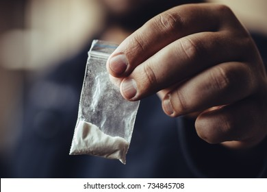 Man hand holds plastic packet or bag with cocaine or another drugs, drug abuse and danger addiction concept, selective focus, toned