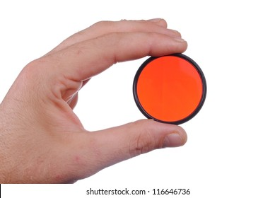 man hand holds a red photographic filter, isolated on white background