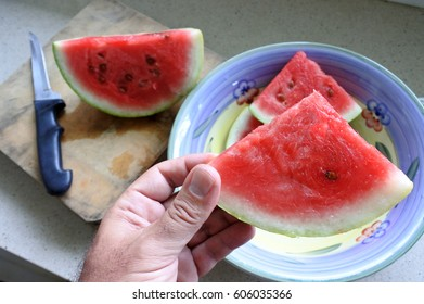 Man hand holds Watermelon slice. Food background