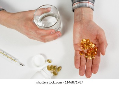 Man hand holds yellow medication capsules of omega 3, pours from a white bottle into palm the fish oil, healthy supplement pills.