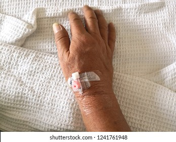 Man hand intravenous cannula inserted resting on the bed
