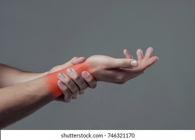 Man hand isolated on grey background. Close-up of man holding his wrist. Experiencing wrist pain.