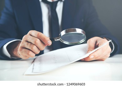 man hand magnifier and documanet on table