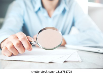 man hand magnifier with documnt on desk