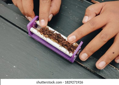 Man hand makes a cigarette with rolling traditional tools, hands closeup.