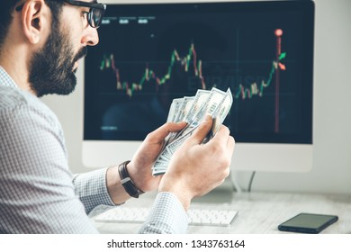 man hand money with  trading computer screen background